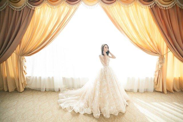 Dívka-nevěsta stojící u okna ve velkém sále